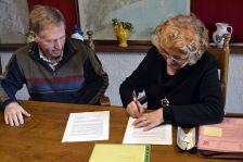 L'alcalde Josep Cuch cedint la primera signatura del conveni a la presidenta en funcions de l'Associació Cívica i Cultural de Cànoves i Samalús, Anna Cortinas.